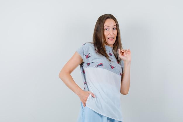 Jeune femme posant avec la main dans la poche en t-shirt, vue de face de la jupe.