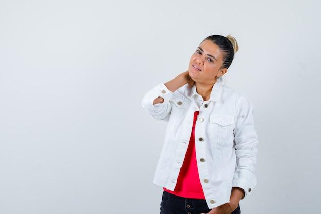 Jeune femme posant avec la main derrière le cou en t-shirt, veste blanche et à la gaieté. vue de face.
