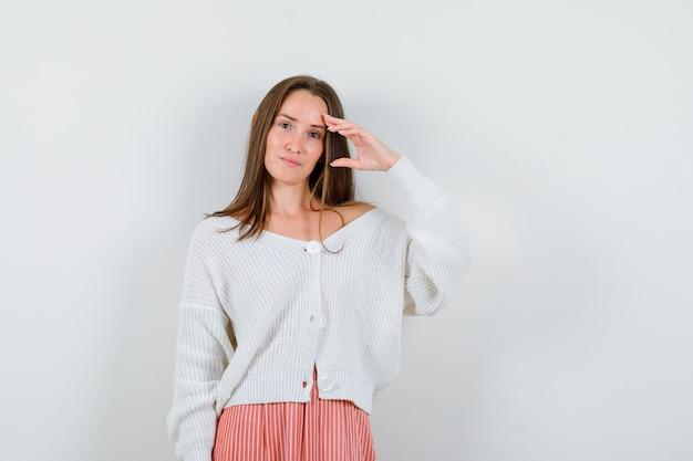 Jeune femme posant avec la main sur la tête en cardigan et jupe à la charmante isolée