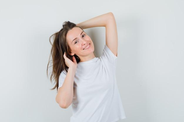 Jeune femme posant avec la main sur la tête en t-shirt blanc et à la séduction