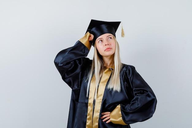 Jeune femme posant avec la main sur la tête en uniforme diplômé et à la pensive