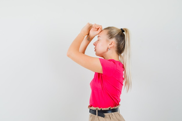Jeune femme posant avec les mains levées sur le front en t-shirt, pantalon et à la charmante. .