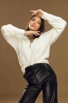 Jeune femme posant à la mode en studio, modèle fille brune sur fond beige en pantalon de cuir. photo de haute qualité