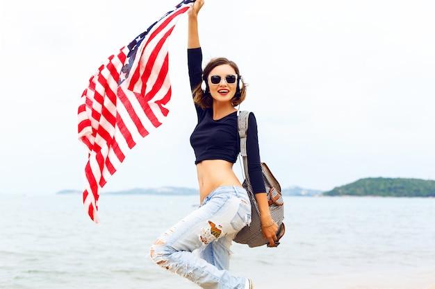 Jeune femme posant sur la plage, écouter de la musique dans ses gros écouteurs élégants