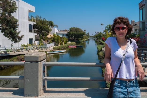 Jeune femme posant pour la caméra avec le canal de venice beach en arrière-plan