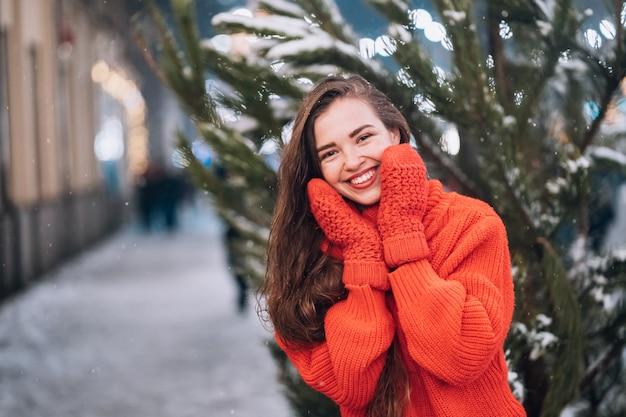 Jeune femme posant près de l'arbre de noël dans la rue