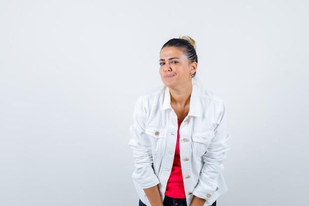 Jeune femme posant en regardant un t-shirt, une veste blanche et l'air joyeux, vue de face.