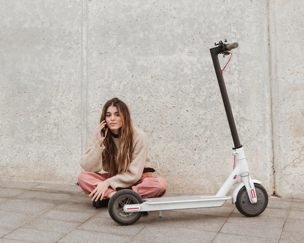 Jeune femme posant avec un scooter électrique