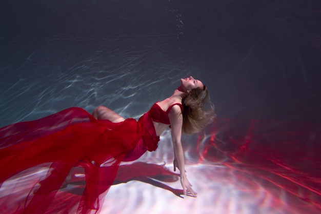 Jeune femme posant sous l'eau dans une robe fluide