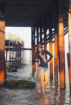 Jeune femme posant sous la jetée.