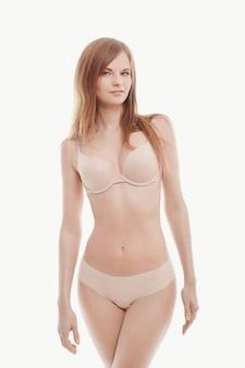 Jeune femme posant en sous-vêtements, soutien-gorge et culotte beige, peau parfaite