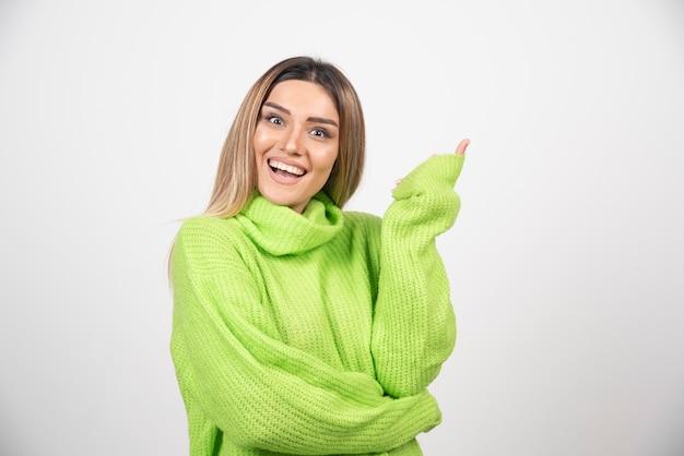 Jeune femme posant en t-shirt vert sur un mur blanc.