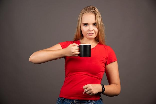 Jeune femme posant avec une tasse vide.