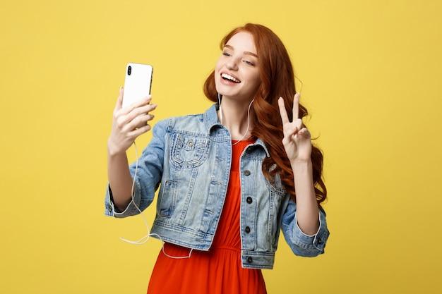 Jeune femme posant tout en se photographiant sur l'appareil photo de téléphone intelligent pour discuter avec un ami