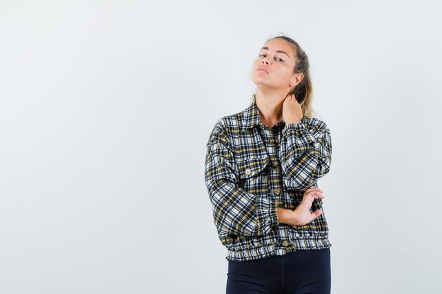 Jeune femme posant tout en tenant la main sur le cou en chemise, short et à la recherche élégante, vue de face.