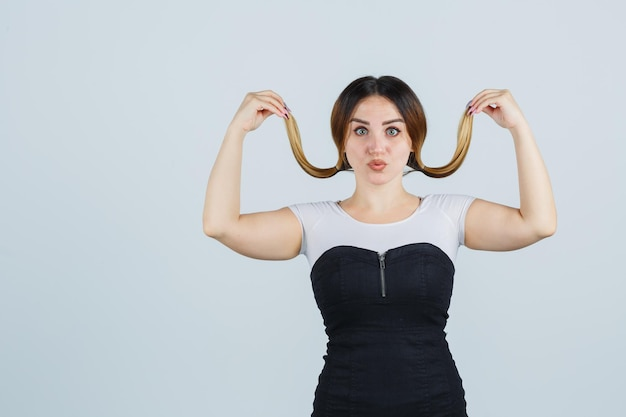 Jeune femme posant tout en tenant des mèches de ses cheveux