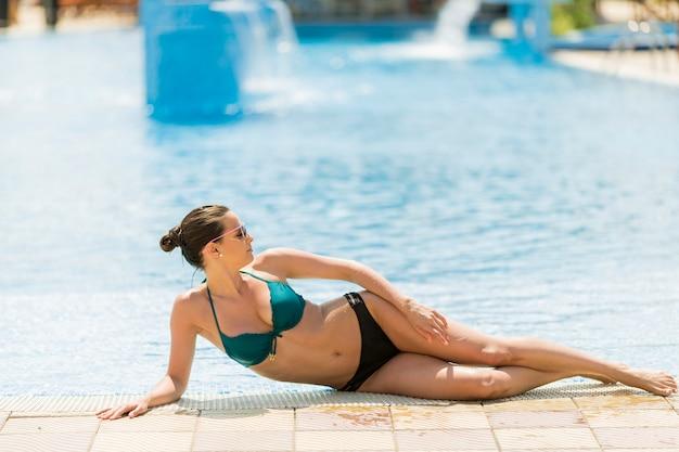 Jeune femme pose au bord de la piscine