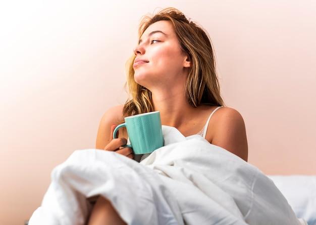 Jeune femme pose dans lit et regarder loin