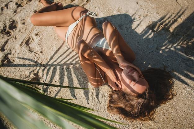 Jeune femme, pose, sur, plage sable, sous, feuille palmier