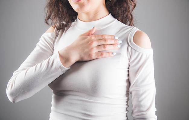 Une jeune femme a posé sa main sur sa poitrine sur une scène grise