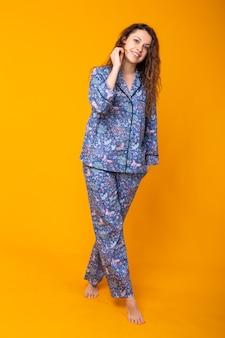 Jeune femme, poser, dans, pyjama, sur, mur jaune