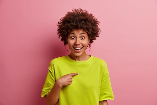 Une jeune femme positive avec des cheveux bouclés pointe sur elle-même, ne peut pas croire qu'elle a été choisie, choisie dans une équipe, a une expression de visage heureuse, porte un t-shirt vert décontracté, isolé sur un mur rose