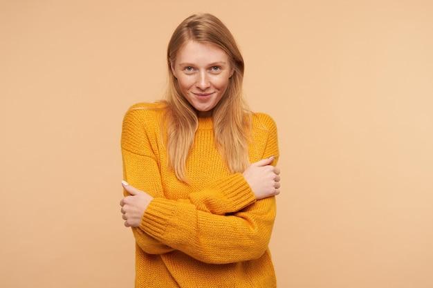 Jeune femme positive avec des cheveux foxy lâches embrassant elle-même et souriant légèrement tout en regardant doucement, debout sur beige