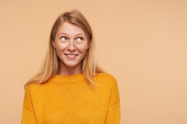 Jeune femme positive avec des cheveux foxy lâches à la recherche positive de côté avec un sourire agréable, portant un pullon moutarde tricoté tout en posant sur beige