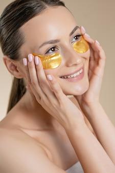 Jeune femme positive avec des coussinets d'or de collagène sous les yeux posant sur fond de studio beige. jolie mannequin appréciant les procédures de beauté. concept de soins de la peau.