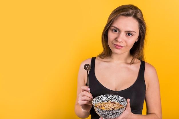 Jeune femme positive avec une cuillère en chocolat et un bol de flocons