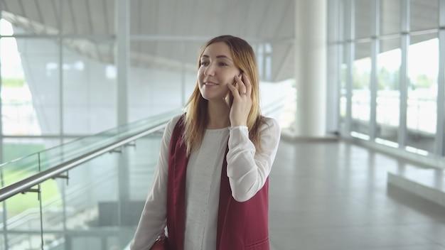 Une jeune femme positive dans des vêtements élégants parle sur un smartphone lors de l'embarquement dans l'avion à l'aéroport