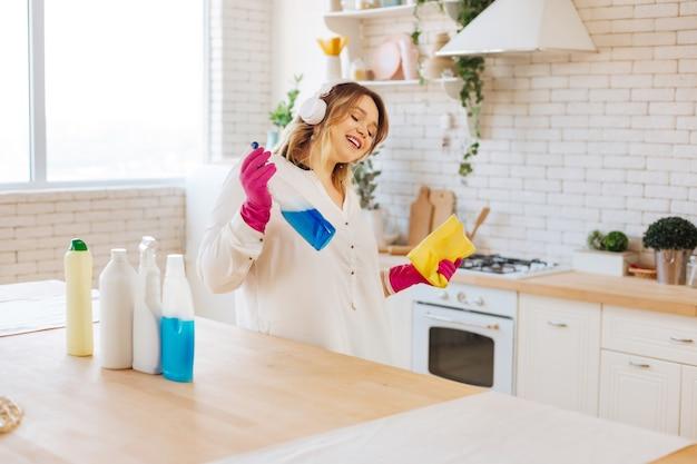 Jeune femme positive écoutant de la musique pendant le nettoyage dans la maison