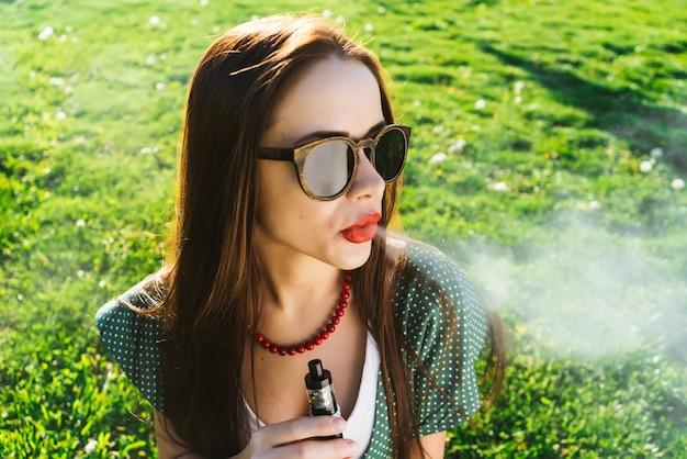 Une jeune femme positive à lunettes de soleil est assise sur la pelouse avec de l'herbe verte brillante, fume, réfléchie