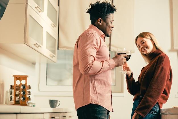 Jeune femme positive pliant la tête vers la droite et souriant tout en buvant du vin dans la cuisine avec un jeune homme