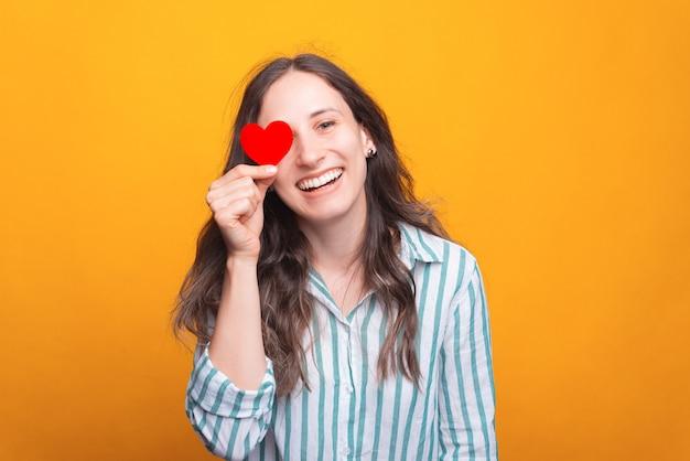 Une jeune femme positive sourit et regarde la caméra tient un cœur en papier près de son œil.