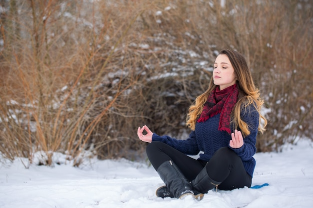 Jeune femme en posture de lotus dans la neige