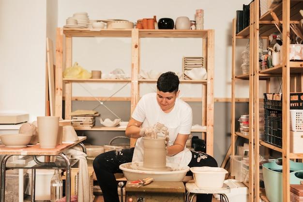 Jeune femme potier façonnant un bord sur le pichet dans l'atelier