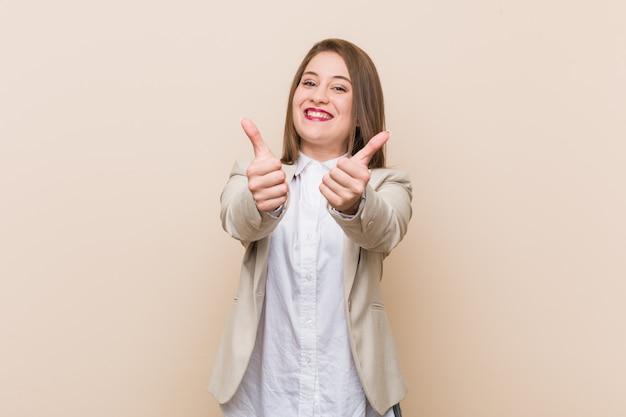 Jeune femme avec le pouce levé, acclame quelque chose, concept de soutien et de respect.