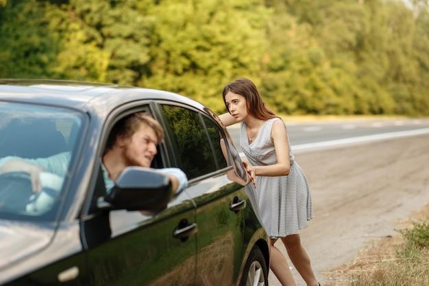 Jeune femme poussant la voiture cassée avec l'homme sur la route, panne