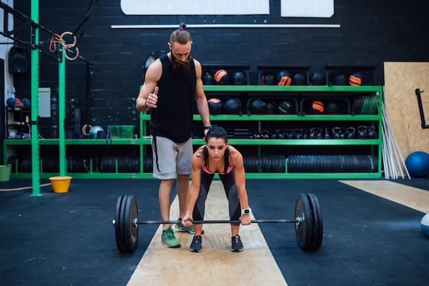 Jeune femme power lifting aidée par son entraîneur personnel