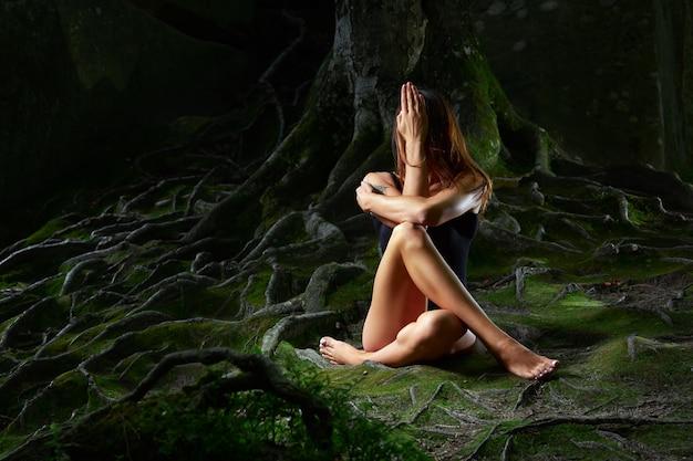 Jeune femme practiver le yoga en plein air