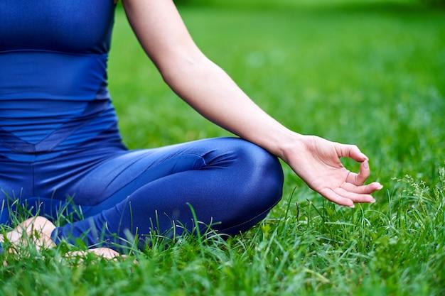 Jeune femme pratiquant la méditation d'yoga dans la nature au parc. pose de lotus. concept de mode de vie santé