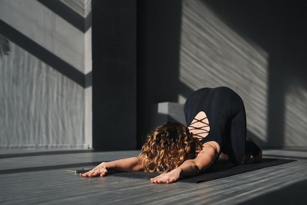 Jeune femme pratiquant des poses de yoga dans un contexte urbain aux beaux jours