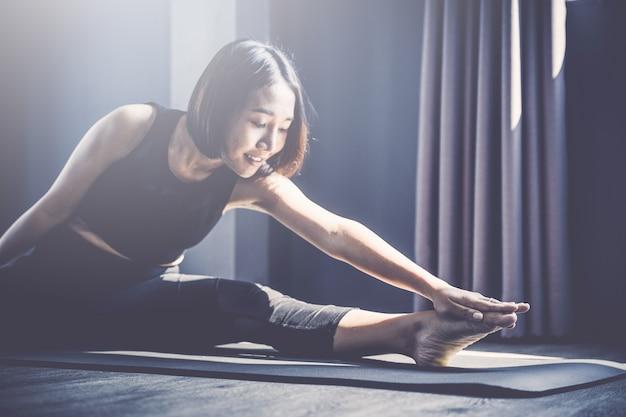 Jeune femme pratiquant le yoga en classe; belle fille ressentant le calme et se détendre en cours de yoga