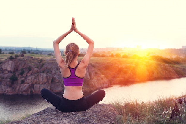 Jeune femme pratiquant le yoga sur la colline au coucher du soleil
