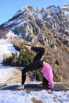 Une jeune femme pratiquant le yoga dans les montagnes