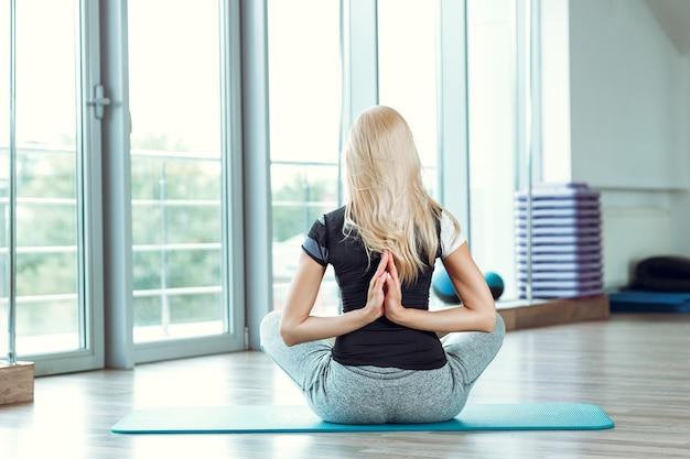 Jeune femme pratiquant le yoga dans la salle de gym. fille joignant les mains derrière le dos