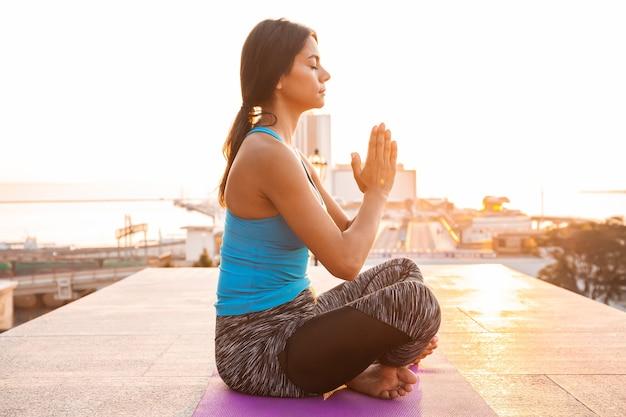 Jeune femme pratiquant le yoga à l'extérieur. concept d'harmonie et de méditation. mode de vie sain