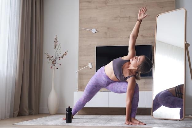 Jeune femme pratiquant le yoga à la maison dans le salon sport yoga et concept de remise en forme