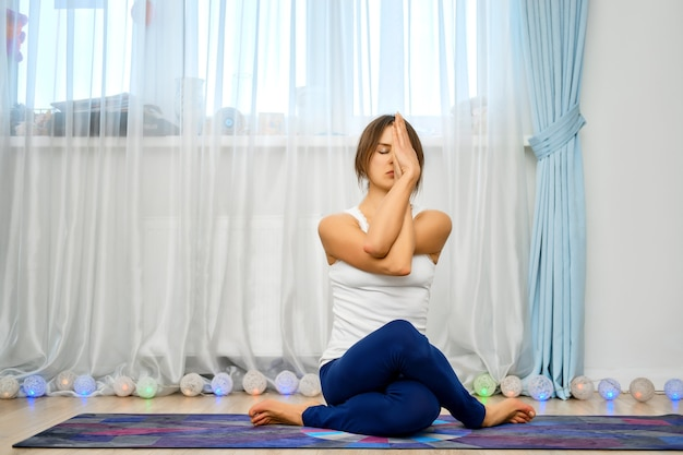 Jeune femme pratiquant le yoga à la maison, est assise avec les mains entrelacées